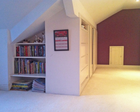Staggered bookshelves in roof space